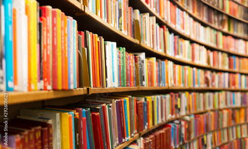 Fototapeta Library with many shelves and books, diminishing perspective and shallow dof