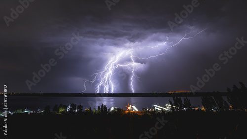 A bright flash of lightning in the sky above the river