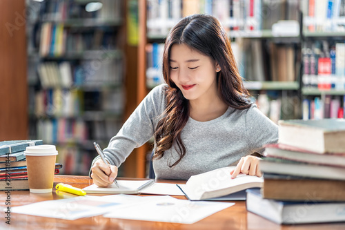 Stampa su Tela  Asian young Student in casual suit reading and doing homework in library of univ