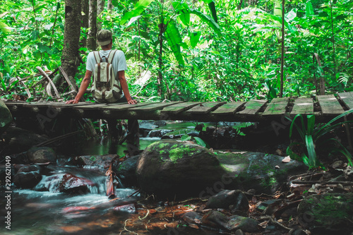 Photo A man with a backpack sitting on bridge wood in the stream looking at the greatness of the forest