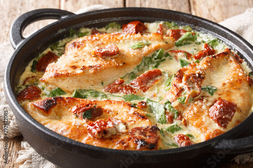 Fotografía  Italian chicken breast with sun-dried tomatoes and spinach in cheese sauce close-up in a pan