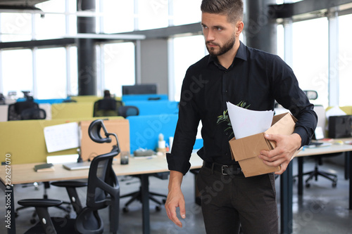 Valokuva  Sad dismissed worker is taking his office supplies with him from office