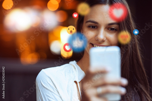 A beautiful young woman blogger, vlogger or influencer is receiving emoji and emoticon reactions in her mobile smart phone device while making a post, sharing or video logging on social media