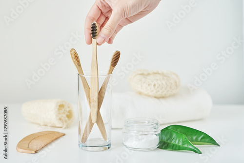Keuken foto achterwand Spa Woman hand take wooden bamboo toothbrush in a bathroom interior. No plastic zero waste concept. Eco friendly toothbrushes in glass, towel, tooth powder and washcloth on white background