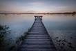 Small wooden bridge with a person meditating in the background on an Ammersee lake in Bavaria