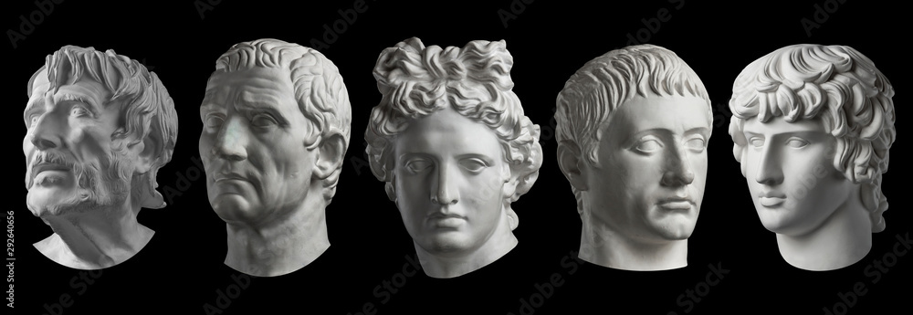 Fototapeta Five gypsum copy of ancient statue heads isolated on a black background. Plaster sculpture mans faces.