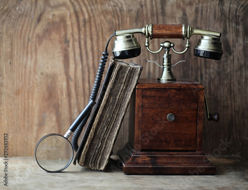 Fototapeta Old telephone and retro book on a wood