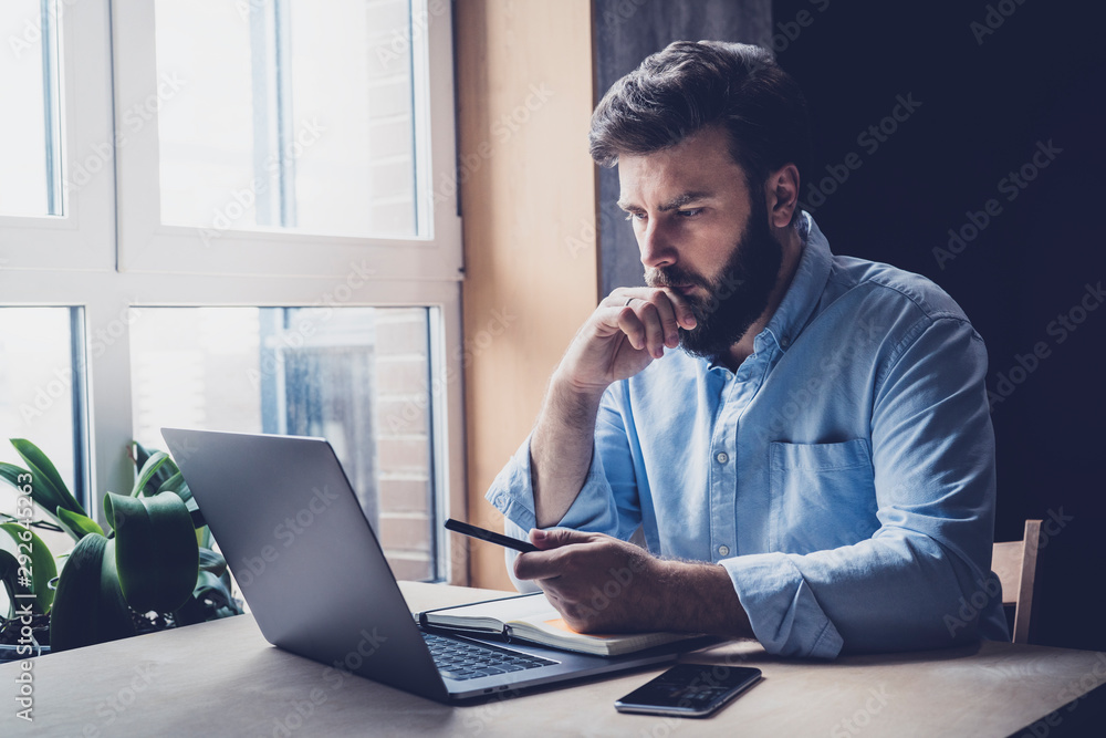 Fototapeta Professional sitting in office in front of laptop. Developer thinking on solutions for work. Home-based student getting distant education. Young serious bearded man in blue shirt working on desktop.