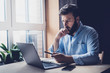 canvas print picture - Professional sitting in office in front of laptop. Developer thinking on solutions for work. Home-based student getting distant education. Young serious bearded man in blue shirt working on desktop.