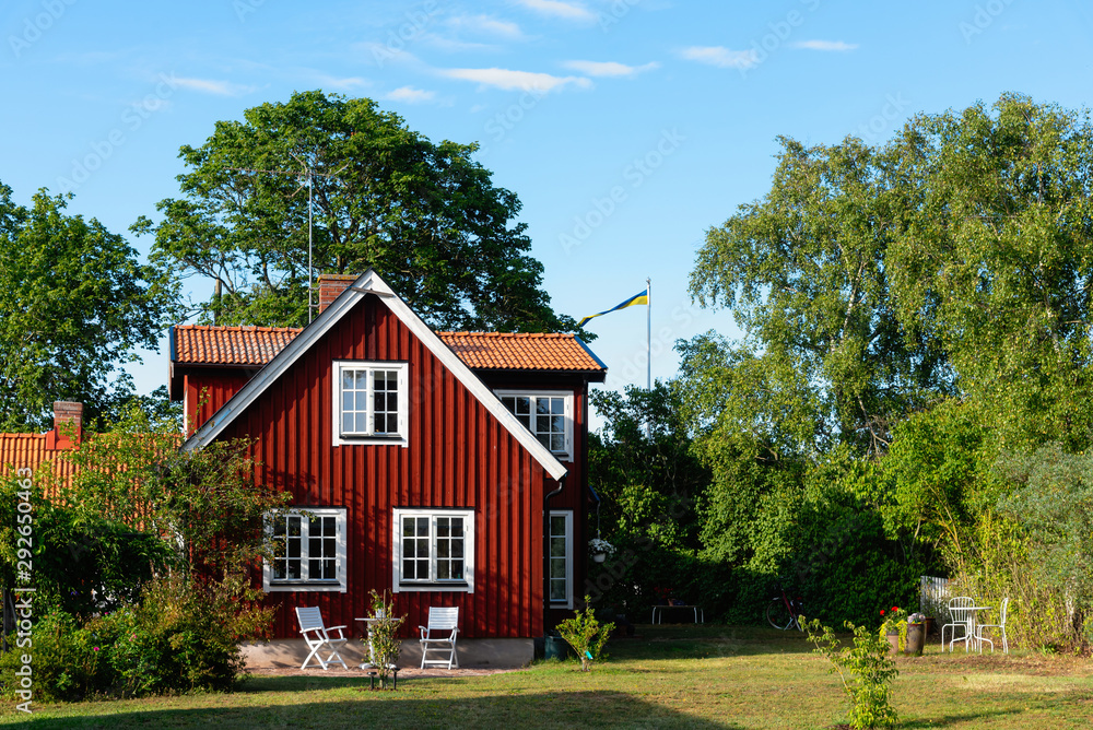 Fototapety, obrazy: Traditional red wooden house in Sweden on the island Oland, in the summer. The house is surrounded by a beautiful, summery garden