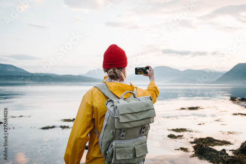 Obraz Traveler wearing yellow raincoat taking photo by smartphone fantastic nord landscape while traveling scandinavia. Man tourist takes a photo great mountain nature - fototapety do salonu