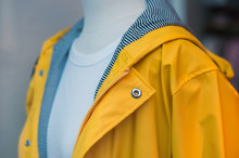 Closeup Of Yellow Rain Coat On Mannequin In Fashion Store Showroom