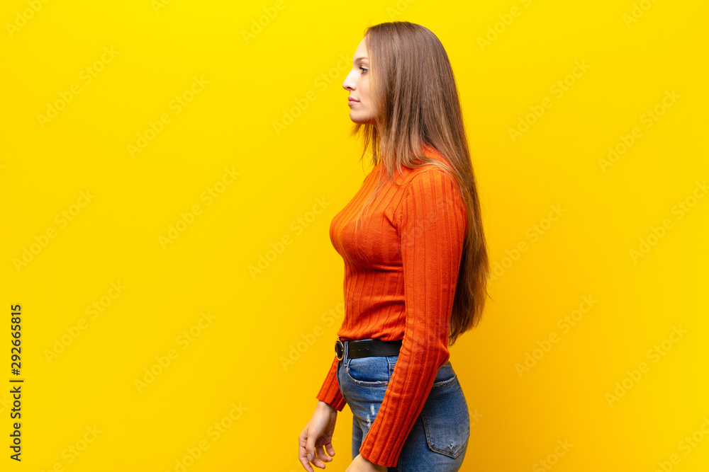 Fototapety, obrazy: young pretty woman on profile view looking to copy space ahead, thinking, imagining or daydreaming against orange background