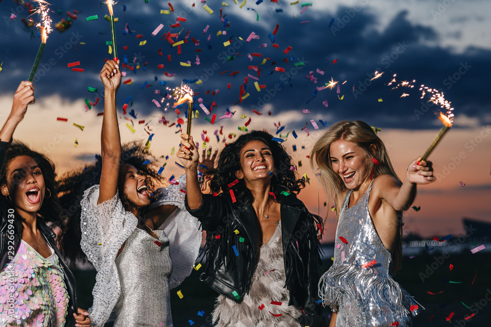Fototapeta Group of four happy women dancing with sparklers under confetti at sunset