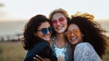 Three Happy Women Wearing Sunglasses Hugging At Evening Outdoors