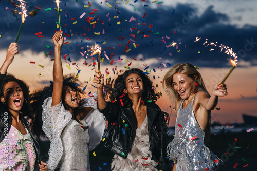 Group of four happy women dancing with sparklers under confetti at sunset - 292669430