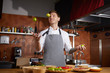 Waist up portrait of handsome professional chef juggling limes while cooking spicy food in Chinese restaurant, copy space