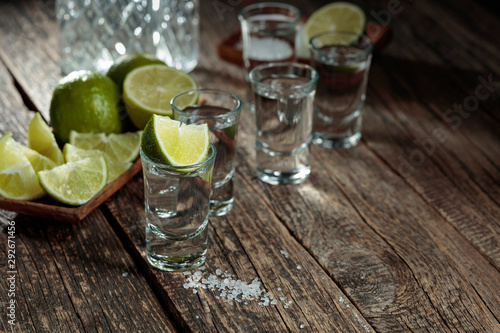 Obraz na plátně  Tequila with  salt and lime on a old wooden background.