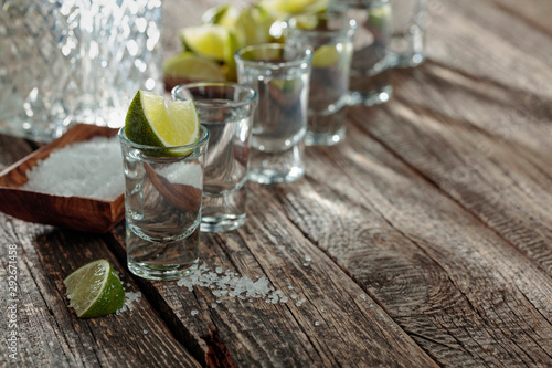 Fotografie, Obraz  Tequila with  salt and lime on a old wooden background.
