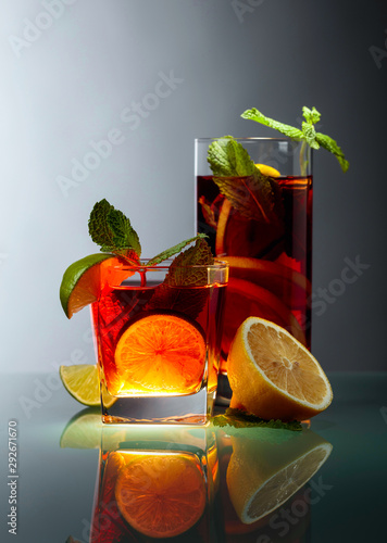 Fototapeta  Cold tea with lime, lemon and mint on a glass table.