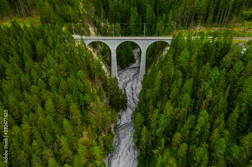 Recess Fitting Forest river Inn River flowing in the forest in Switzerland. Aerial view from drone on an old railway bridge viaduct in the mountains