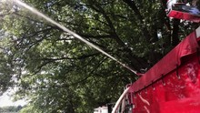 A Red Firetruck Sprays A Stron...