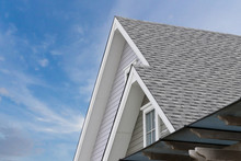 Roof Shingles On Top Of The House Against Blue Sky With Cloud, Dark Asphalt Tiles On The Roof Background.
