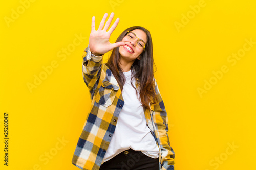 Obraz young  pretty woman smiling and looking friendly, showing number five or fifth with hand forward, counting down against orange wall - fototapety do salonu