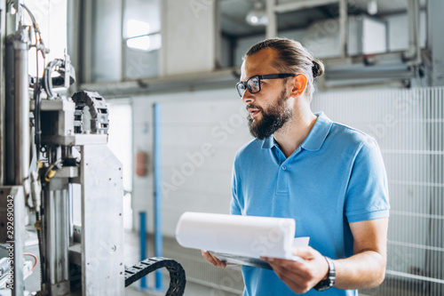 Fotomural  Young engeneer manager with beard checking manufactory, workplace and machinery on big factory