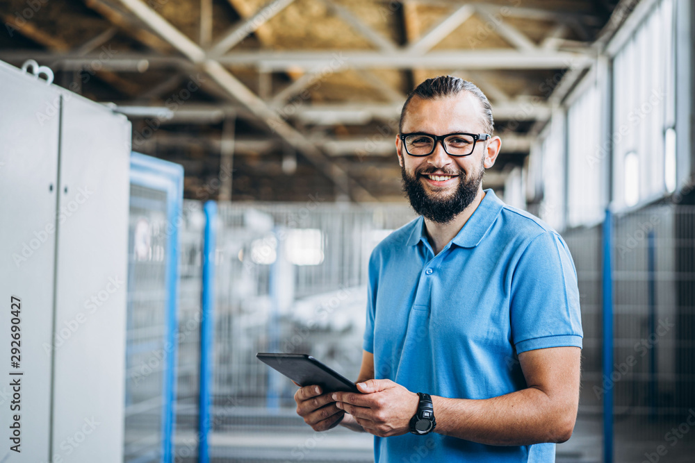 Fototapeta Young engeneer manager with beard checking manufactory, workplace and machinery on big factory.
