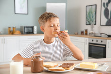 Funny Little Boy Eating Tasty Toasts With Chocolate Spreading In Kitchen