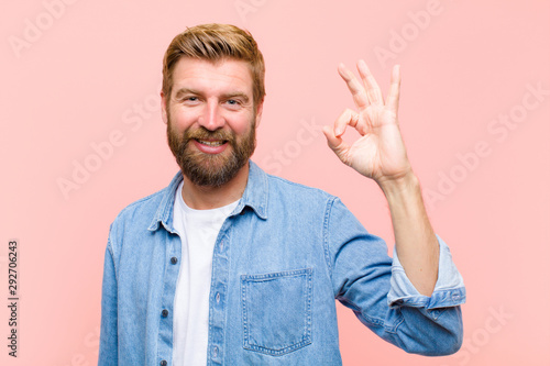 Fotografie, Obraz  young blonde adult man feeling happy, relaxed and satisfied, showing approval wi