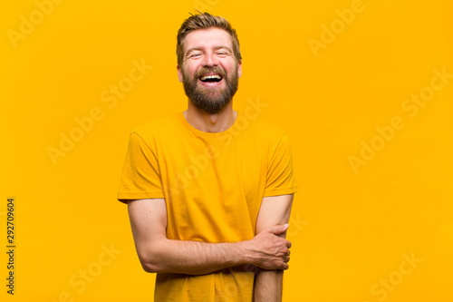Fotografía  young blonde man laughing shyly and cheerfully, with a friendly and positive but