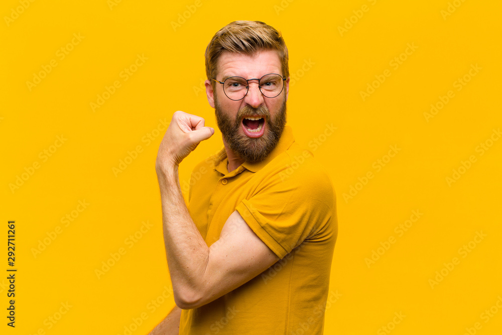 Fototapeta young blonde man feeling happy, satisfied and powerful, flexing fit and muscular biceps, looking strong after the gym against orange wall
