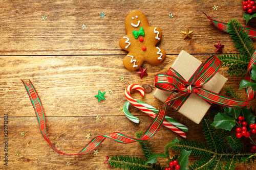 Canvas Prints London Christmas background with gift box, gingerbread cookies, branches of holly and fir on wooden background. Winter festive concept. Flat lay, copy space.