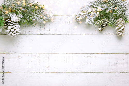 Foto auf Gartenposter Baume Christmas tree branch with pine cone in snow and retro style clock on a white wooden background. Winter or Christmas festive concept. Flat lay, copy space.