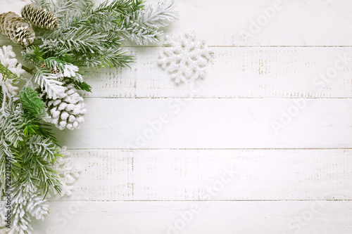 Christmas tree branch with pine cone in snow and retro style clock on a white wooden background. Winter or Christmas festive concept. Flat lay, copy space.
