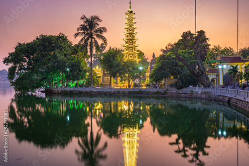 Hanoi buddhist pagoda on West Lake, colorful sunset, illuminated temple, water reflection. Chua Tran Quoc on Ho Tay at Hanoi, Vietnam travel.