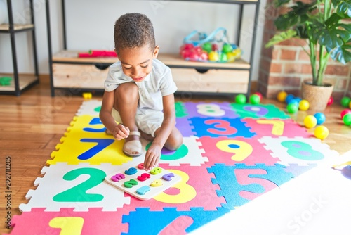 Fotomural  Beautiful african american toddler playing with maths game using numbers at kind