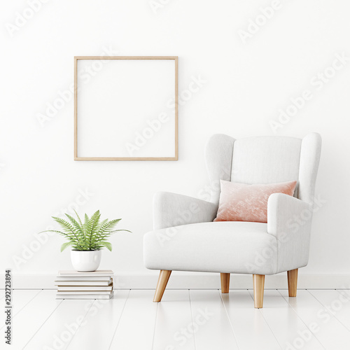 Fototapeta  Poster mockup with square wooden frame hanging on the wall in living room interior with armchair, pink pillow and green fern plant on empty white background