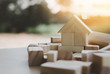 canvas print picture - house from natural color wooden block on the stack of wooden blocks with orange light effect