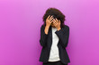 canvas print picture - young black business woman covering eyes with hands with a sad, frustrated look of despair, crying, side view