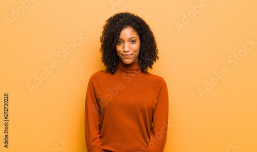 Fotografía young pretty black woman smiling positively and confidently, looking satisfied,