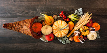 Thanksgiving Cornucopia Filled With Autumn Vegetables And Pumpkins. Above View Against A Dark Wood Background.