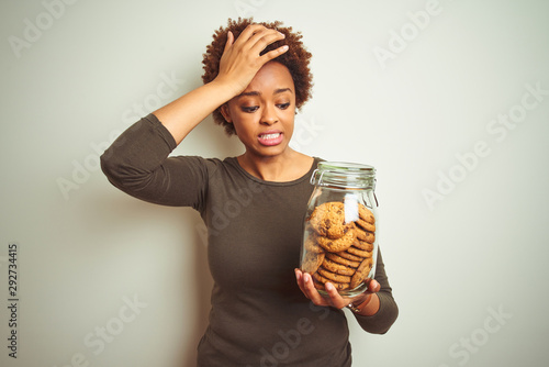 African american woman holding jar of chocolate chips cookies over isolated background stressed with hand on head, shocked with shame and surprise face, angry and frustrated Billede på lærred