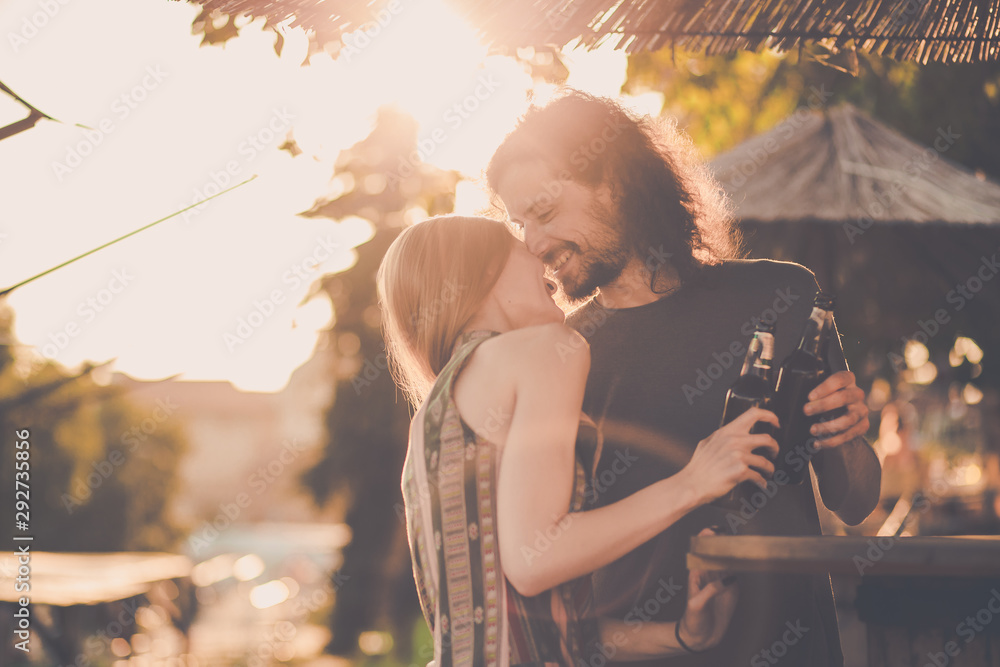 Fototapety, obrazy: Hipster couple drinking beer in a bar with afternoon light under bar umbrella.