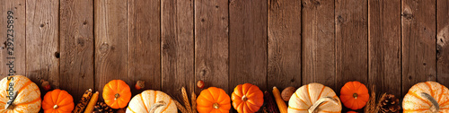 Autumn bottom border banner of pumpkins and fall decor on a rustic wood background with copy space - 292735899