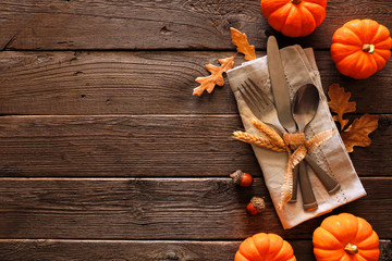 Autumn harvest or thanksgiving table scene with silverware, napkin, leaves and pumpkin border against a rustic dark wood background