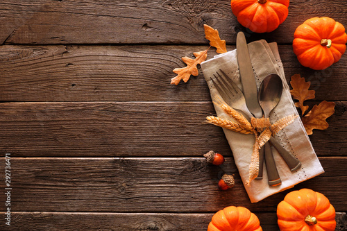 Wall Murals Autumn Autumn harvest or thanksgiving table scene with silverware, napkin, leaves and pumpkin border against a rustic dark wood background