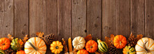 Autumn Bottom Border Banner Of Pumpkins, Gourds And Fall Decor On A Rustic Wood Background With Copy Space